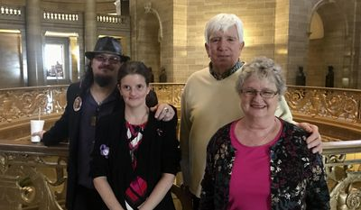 Jeff Barfield, Stacey Owens, Regina Wood and Jim Wood, left to right, pose for a photo in the rotunda of the Missouri Capitol in Jefferson City on Wednesday, Jan. 11, 2017. The families joined forces to sponsor a bill streamlining the Missouri Amber Alert system after Barfield and Owens' 10-year-old daughter, Hailey Owens, was kidnapped and killed in 2014. Regina and Jim Wood are the parents of the man suspected of killing her, who say a faster Amber Alert could have helped save Hailey Ownens' life. (AP Photo/Katie Kull)