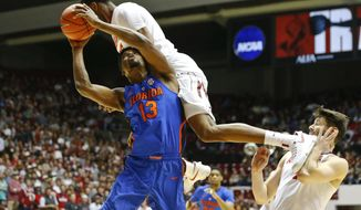 Florida forward Kevarrius Hayes jumps up to score and is fouled by Alabama forward Donta Hall and Hall kicked his teammate Alabama guard Riley Norris during the first half of an NCAA college basketball game, Tuesday, Jan. 10, 2017, in Tuscaloosa, Ala. Florida won 80-67. (AP Photo/Brynn Anderson)