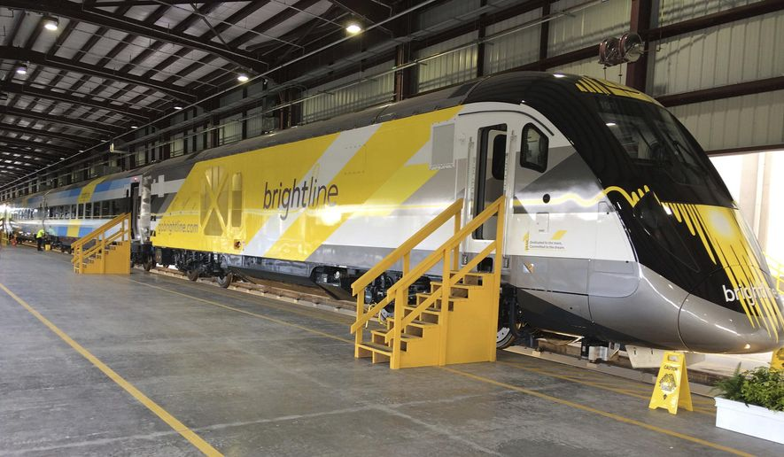 Engine and cars are seen at a Brightline maintenance facility in West Palm Beach, Fla., Wednesday, Jan. 11, 2017. The company building a passenger rail line between Miami and Orlando is scheduled to show off its first engine and cars. Brightline plans to show reporters the engine and cars Wednesday in West Palm Beach. Test runs between West Palm Beach and Miami are expected to begin soon. There will also be a stop in Fort Lauderdale. (AP Photo/Terry Spencer)