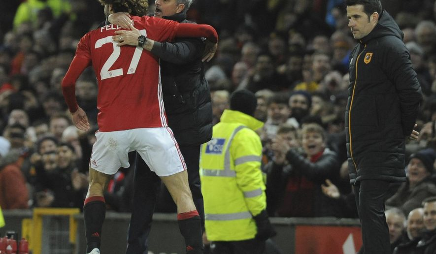 Manchester United's manager Jose Mourinho, second right, hugs his player Manchester United's Marouane Fellaini after he scored his sides second goal of the game, as Hull's manager Marco Silva looks on during the English League Cup semifinal, 1st leg, soccer match between Manchester United and Hull at Old Trafford stadium in Manchester, England, Tuesday, Jan. 10, 2017. (AP Photo/Rui Vieira)