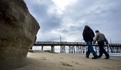 People out for a stroll make their way south near the Newport Beach Pier past some beach erosion due to in part to the recent storms and the King tide early Tuesday morning, Jan. 10, 2017, in Newport Beach, Calif. (Mark Rightmire/The Orange County Register via AP)