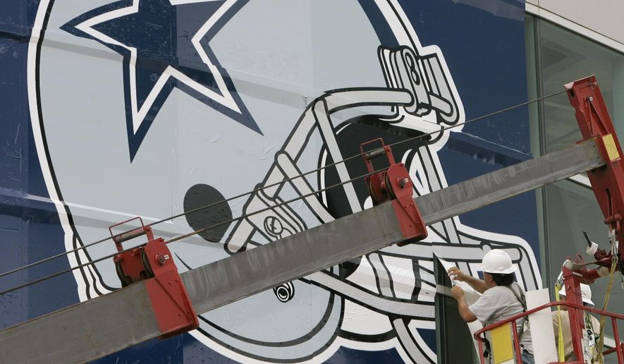FILE - In this July 24, 2007, file photo, workers hang a Dallas Cowboys logo on the Alamodome in preparation for football training camp in San Antonio. WFAA-TV reported on Jan. 10, 2017 that a Texas baby hospitalized with a congenital heart defect calms down when watching Cowboys games. (AP Photo/Eric Gay, File)