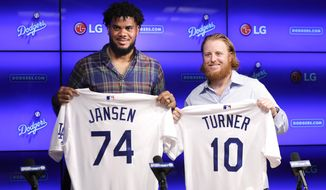 Los Angeles Dodgers closer Kenley Jansen, left, and third baseman Justin Turner pose with their jerseys following a news conference Wednesday, Jan. 11, 2017, in Los Angeles. The two re-signed with the team as free agents. (AP Photo/Jae C. Hong)