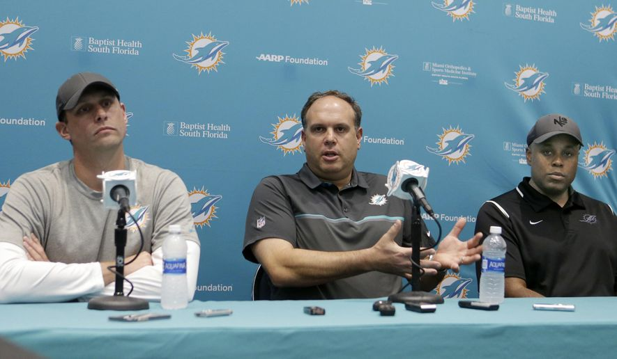 Miami Dolphins NFL football executive vice president of football operations Mike Tannenbaum, center, flanked by head coach Adam Gase, left, and general manager Chris Grier, right, talks to reporters during a news conference, Wednesday, Jan. 11, 2017, in Sunrise, Fla. Tannenbaum says he was pleased with the team's first playoff berth in eight years, but a lot of work remains to be do to overtake the New England Patriots in the AFC East. (AP Photo/Alan Diaz)