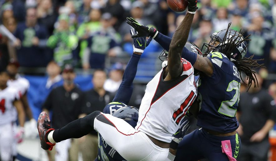 FILE - In this Oct. 16, 2016, file photo, Seattle Seahawks cornerback Richard Sherman, right, and Earl Thomas (obscured) break up a pass intended for Atlanta Falcons wide receiver Julio Jones (11) in the second half of an NFL football game, in Seattle. Jones and the Falcons get another shot at Seattle in Saturday's divisional round playoff game.  (AP Photo/Elaine Thompson, File)