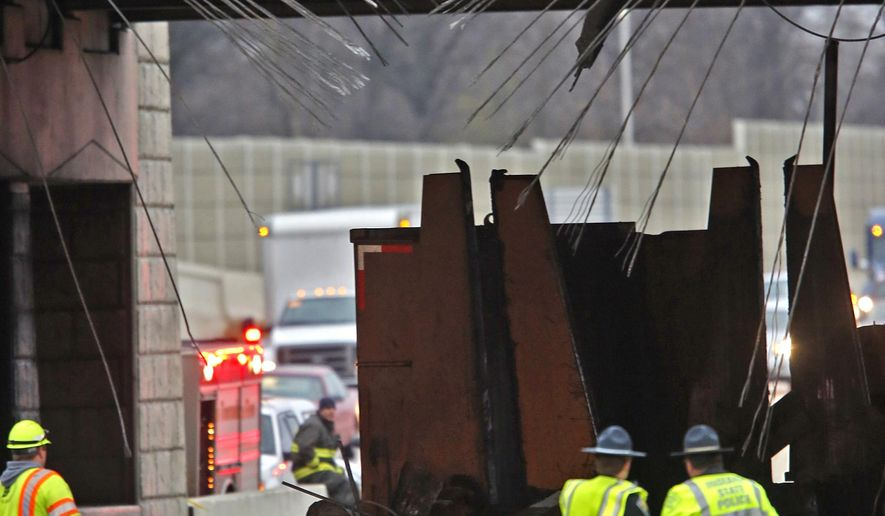 Investigation and cleanup continues at the Rockville Rd. overpass at I-465, Tuesday, Jan. 10, 2017, in Indianapolis.  A car compactor being hauled by a semi activated and struck beams under the overpass, showering the highway with concrete and leading officials to close miles of northbound lanes Tuesday. (Kelly Wilkinson/The Indianapolis Star via AP)