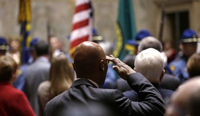 Rep. John Lovick, D-Mill Creek, salutes the flag carried by an honor guard at a joint session of the Legislature Wednesday, Jan. 11, 2017, in Olympia, Wash. (AP Photo/Elaine Thompson)