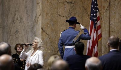 Singer Judy Collins, left, sings the national anthem as a member of the Washington State Patrol honor guard salutes the flag to begin a joint session of the Legislature, Wednesday, Jan. 11, 2017, in Olympia, Wash. (AP Photo/Elaine Thompson)