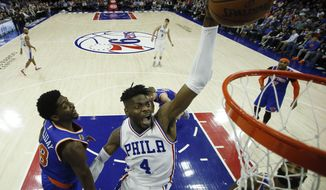 Philadelphia 76ers' Nerlens Noel (4) goes up for a dunk against New York Knicks' Justin Holiday (8) during the first half of an NBA basketball game, Wednesday, Jan. 11, 2017, in Philadelphia. (AP Photo/Matt Slocum)