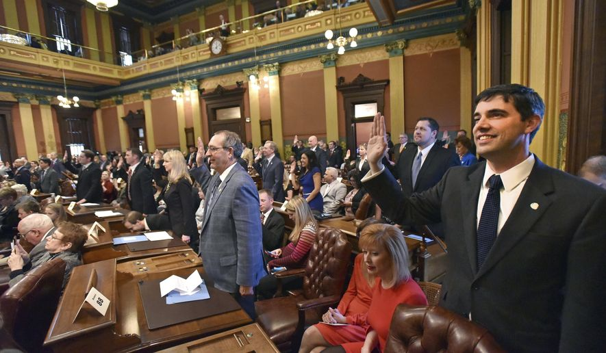 Rep. Jim Lilly, R-Holland takes his oath of office with other Representatives as the Michigan House of Representatives convenes to start the new year at the Capitol in Lansing, Mich., Wednesday, Jan. 11, 2017. (Dale G. Young/Detroit News via AP)