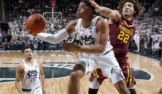 Michigan State's Miles Bridges, center, puts up a reverse layup against Minnesota's Reggie Lynch (22) as Michigan State's Kenny Goins, left, watches during the first half of an NCAA college basketball game, Wednesday, Jan. 11, 2017, in East Lansing, Mich. (AP Photo/Al Goldis)