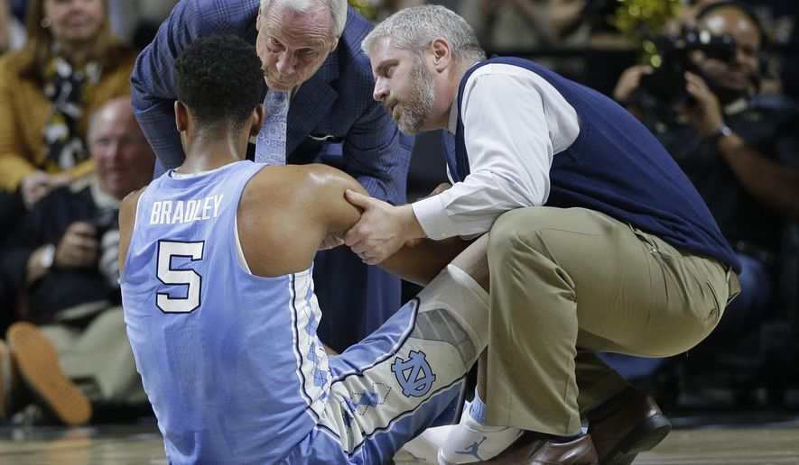 North Carolina coach Roy Williams, top left, checks on Tony Bradley (5) during the first half of an NCAA college basketball game against Wake Forest in Winston-Salem, N.C., Wednesday, Jan. 11, 2017. (AP Photo/Chuck Burton)
