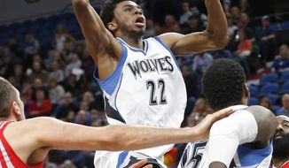 Minnesota Timberwolves' Andrew Wiggins, center, lays up against the Houston Rockets during the first quarter of an NBA basketball game Wednesday, Jan. 11, 2017, in Minneapolis. (AP Photo/Jim Mone)