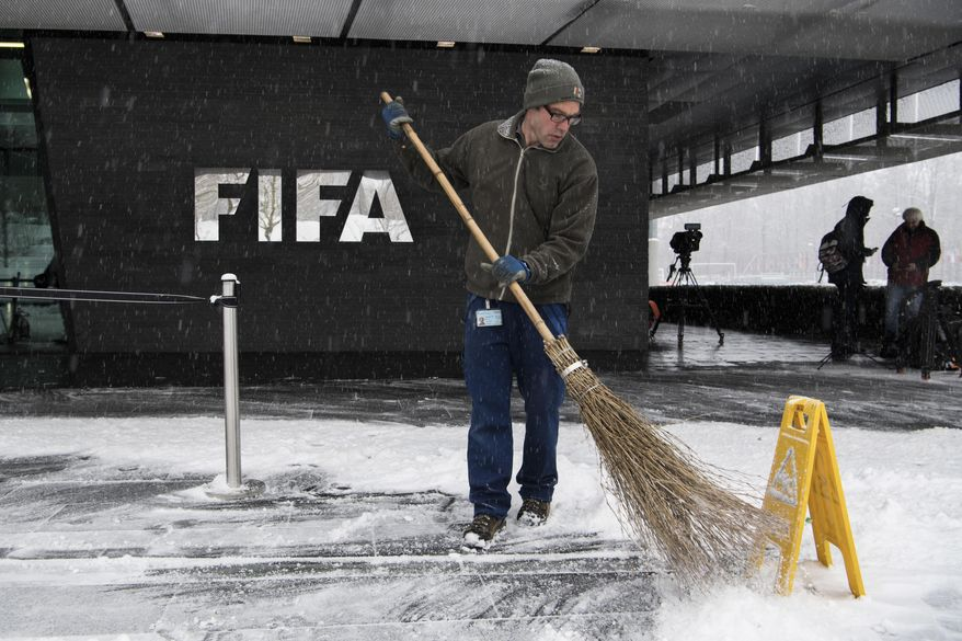 A man sweeps snow next to the FIFA logo on the occasion the FIFA Council meeting at the Home of FIFA in Zurich, Switzerland, Tuesday, January 10. FIFA will expand the World Cup to 48 teams, adding 16 extra nations to the 2026 tournament which is likely to be held in North America. President Gianni Infantino's favored plan — for 16 three-team groups with the top two advancing to a round of 32 — was unanimously approved Tuesday, Jan. 10, 2017 by the FIFA Council. (Ennio Leanza/Keystone via AP)