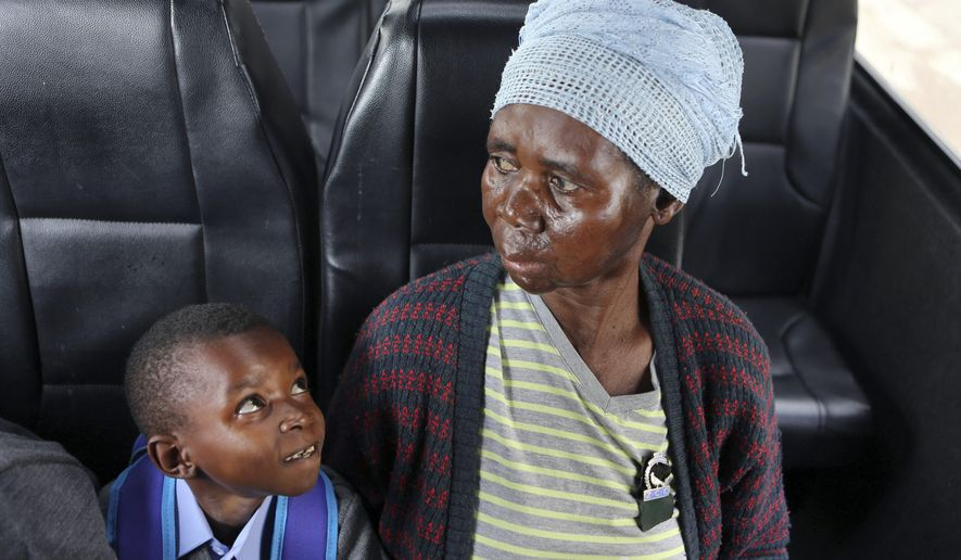 10-year-old Tumi Tlebjane looks up at his grandmother, 64-year-old Helen Tlebjane, both from Nkosi's Haven, south of Johannesburg, as he heads for his first day of his school career, Wednesday, Jan. 11, 2017. Tumi will start his studies at a Johannesburg school for students with special learning needs. (AP Photo/Denis Farrell)