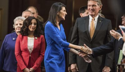 South Carolina Gov. Nikki Haley, center, with Rep. Katie Arrington, R-Dorchester, left, and Sen. Harvey Peeler, R-Cherokee, greets lawmakers before delivering the state of the state in the House chamber at the state Capitol, Wednesday, Jan. 11, 2017, in Columbia, S.C. (AP Photo/Sean Rayford)