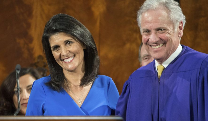 South Carolina Gov. Nikki Haley, left, smiles with Lt. Gov. Henry McMaster, right, after delivering the state of the state in the House chamber at the South Carolina Statehouse Wednesday, Jan. 11, 2017, in Columbia, S.C. (AP Photo/Sean Rayford)