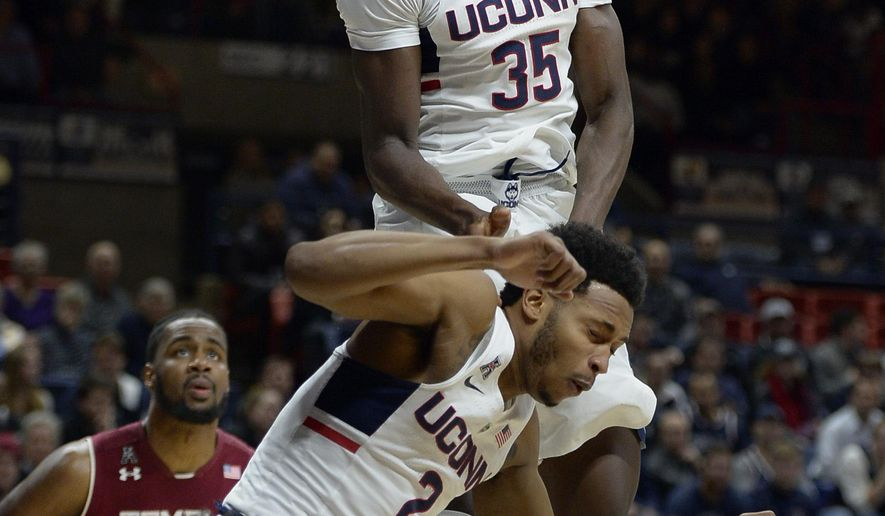 Connecticut's Amida Brimah, top reacts after blocking a shot by Temple's Quinton Rose, bottom, as teammate Jalen Adams, falls below, in the first half of an NCAA college basketball game, Wednesday, Jan. 11, 2017, in Storrs, Conn. (AP Photo/Jessica Hill)