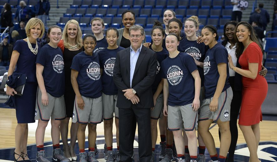 Connecticut head coach Geno Auriemma poses with his team for a photograph at the end of an NCAA college basketball game against South Florida, Tuesday, Jan. 10, 2017, in Hartford, Conn. (AP Photo/Jessica Hill)
