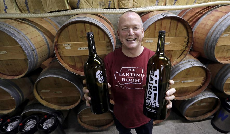"In this photo taken Tuesday, Jan. 10, 2017, winemaker Paul Beveridge displays the type of wine ""growler"" bottle he would like to see available to consumers, at his winery in Seattle.  Wine drinkers are one step closer to being able to purchase and refill their favorite pours in reusable growlers closer to home instead of making a trip to the winery. Some state winemakers are pushing House Bill 1039 as a way to expand wine sales and reduce the carbon footprint of wine bottles. If approved, consumers would be able to bring or buy refillable growlers at any business that has the license to sell wine. (AP Photo/Elaine Thompson)"