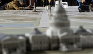 A Capitol building model is seen in foreground as news photographers take photos of a model of the White House, above center, on a giant planning map during a media tour highlighting inaugural preparations being made by the Joint Task Force-National Capital Region for military and civilian planners, Wednesday, Dec. 14, 2016, at the DC Armory in Washington. (AP Photo/Andrew Harnik)
