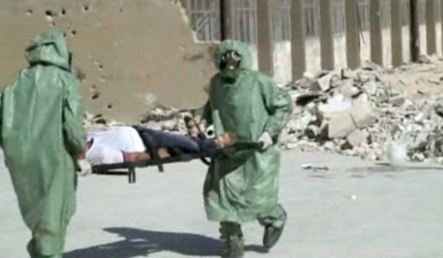 FILE - This image made from an AP video posted on Wednesday, Sept. 18, 2013 shows shows Syrians in protective suits and gas masks conducting a drill on how to treat casualties of a chemical weapons attack in Aleppo, Syria. The Islamic State group is aggressively pursuing development of chemical weapons, setting up a branch dedicated to research and experiments with the help of scientists from Iraq, Syria and elsewhere in the region, according to Iraqi and U.S. intelligence officials. (AP Photo via AP video, File)