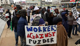 About 50 fast food workers protest the nomination of former Hardees CEO Andrew Puzder to lead the U.S. Department of Labor on Thursday, Jan. 12, 2017, outside the current headquarters of the fast food chain in downtown St. Louis. Fast food workers claim Puzder is unfit for the position because of his policies toward employees as Hardees boss. (Christian Gooden/St. Louis Post-Dispatch via AP)
