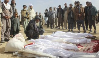 FILE -- In this Nov. 4, 2016 file photo, Afghan villagers gather around several victims' bodies who were killed during clashes between Taliban and Afghan security forces in the Taliban-controlled, Buz-e Kandahari village in Kunduz province, Afghanistan. In a statement released Thursday, Jan. 12, 2017, the U.S. military in Afghanistan said the results of its investigation into the November firefight with the Taliban in Kunduz province show that American troops had fired on Afghan homes, killing 33 civilians. (AP Photo/Najim Rahim, File)