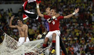 FILE - In this Sunday, Jan. 31, 2010 file photo, Egypt soccer players sit atop the goal posts as they celebrate their victory in the African Cup of Nations final soccer match against Ghana, in Luanda, Angola. The African Cup of Nations returns to Gabon for the second time in five years with the kickoff on Saturday Jan. 14, 2017 and the final on Feb. 5. (AP Photo/Darko Bandic, File)