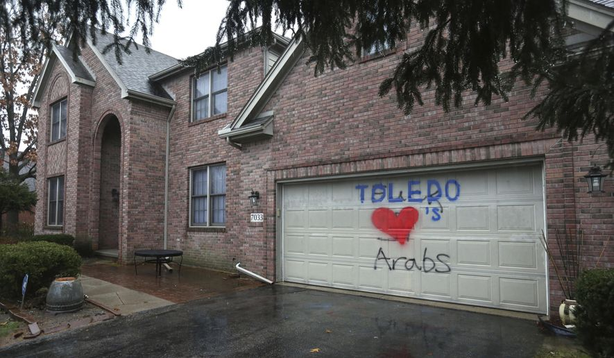 EDS NOTE: VULGAR LANGUAGE BEHIND THE WORK TOLEDO - A heart, painted over a swastika and graffiti cursing Arabs, is pictured on the garage door of the Eltatwy family home  in Sylvania Township, Ohio, Thursday, Jan. 12, 2017. Resident Souheir Eltatawy said her daughter painted over the hateful graffiti. Vandals painted the swastika and graffiti on the garage sometime on Tuesday evening, Jan. 10. (Dave Zapotosky/The Blade via AP)