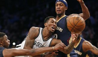 New Orleans Pelicans forward Terrence Jones, left, and New Orleans Pelicans forward Dante Cunningham (33) double team Brooklyn Nets forward Rondae Hollis-Jefferson (24) as they sandwich him beneath the Nets basket in the second half of an NBA basketball game, Thursday, Jan. 12, 2017, in New York. The Pelicans defeated the Nets 104-95. (AP Photo/Kathy Willens)