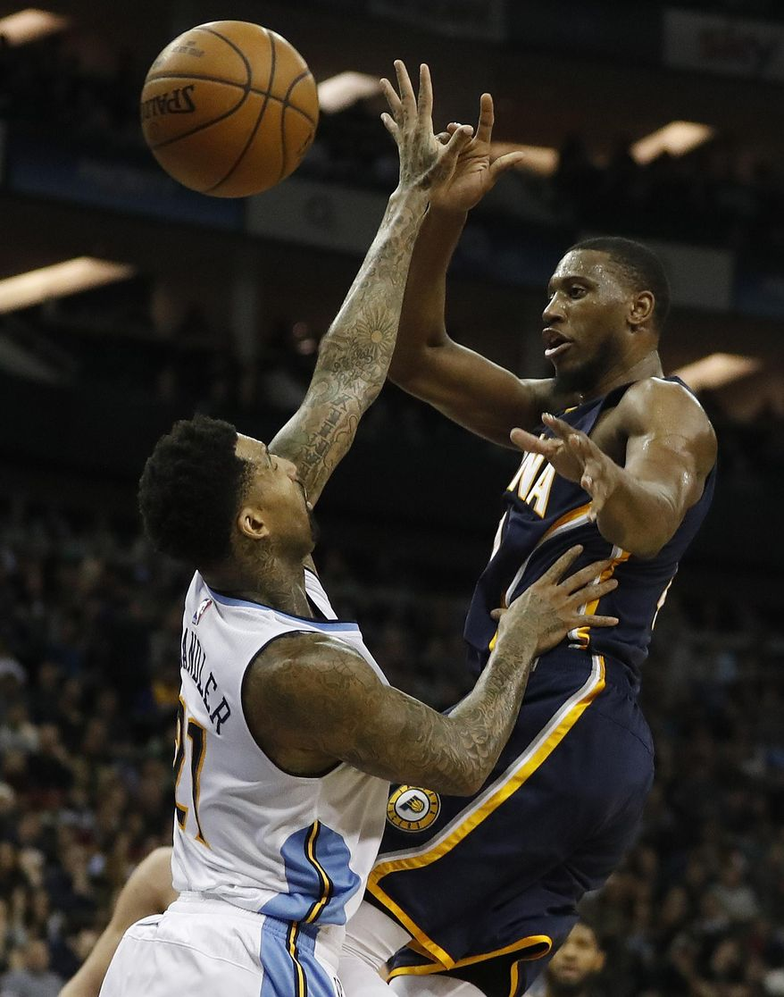 Denver's Wilson Chandler, left, blocks Indiana's Thaddeus Young during the NBA basketball match between Indiana Pacers and Denver Nuggets in London, Thursday, Jan. 12, 2017.(AP Photo/Kirsty Wigglesworth)