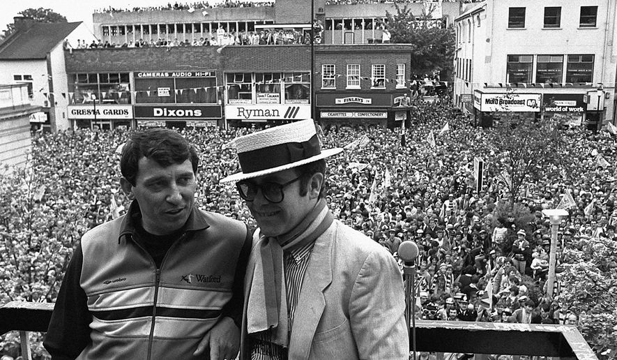 FILE - In this file photo dated May 20, 1984, Watford Football Club Chairman and pop singer Elton John, right, stands with team manager Graham Taylor on a balcony overlooking a crowd of well wishers.  Former England soccer coach Graham Taylor has died of a suspected heart attack aged 72, according to a family statement Thursday Jan. 12, 2017.  (PA via AP)