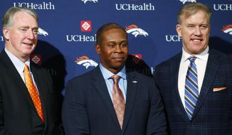 Flanked by Joe Ellis, left, chief executive officer of the Denver Broncos, and general manager John Elway, Vance Joseph, center, smiles after being introduced as the new head coach of the team during a news conference at the team's headquarters Thursday, Jan. 12, 2017, in Englewood, Colo. (AP Photo/David Zalubowski)
