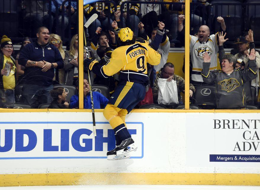 Nashville Predators left wing Filip Forsberg (9), of Sweden, leaps into the glass as he celebrates his goal against the Boston Bruins during the second period of an NHL hockey game Thursday, Jan. 12, 2017, in Nashville, Tenn. (AP Photo/Mark Zaleski)