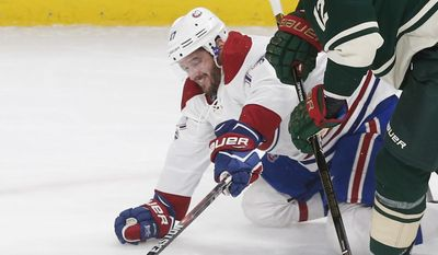 Montreal Canadiens' Torrey Mitchell, left, and Minnesota Wild's Eric Staal compete to reach the puck during the first period of an NHL hockey game Thursday, Jan. 12, 2017, in St. Paul, Minn. (AP Photo/Jim Mone)