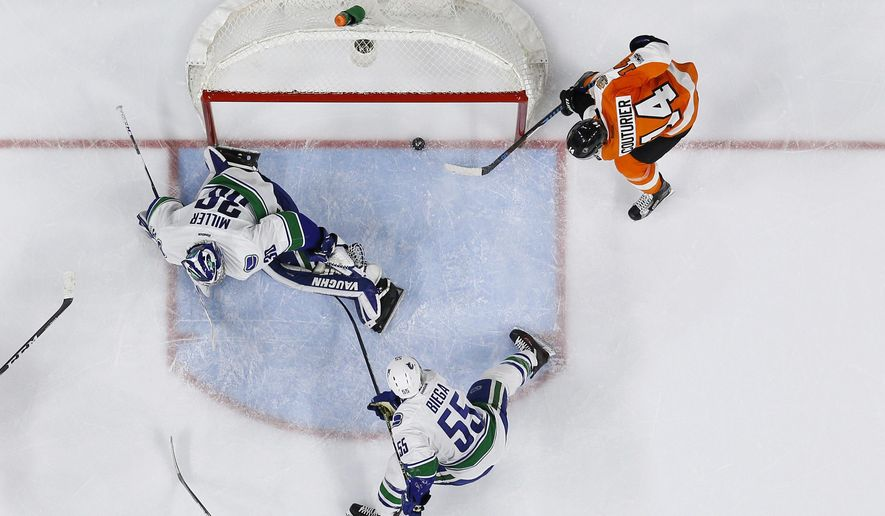 Philadelphia Flyers' Sean Couturier (14) scores a goal past Vancouver Canucks' Ryan Miller (30) as Alex Biega (55) looks on during the second period of an NHL hockey game, Thursday, Jan. 12, 2017, in Philadelphia. (AP Photo/Matt Slocum)