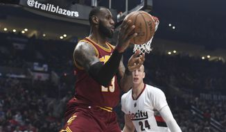 Cleveland Cavaliers forward LeBron James passes the ball as Portland Trail Blazers center Mason Plumlee defends during the first half of an NBA basketball game in Portland, Ore., Wednesday, Jan. 11, 2017. (AP Photo/Steve Dykes)