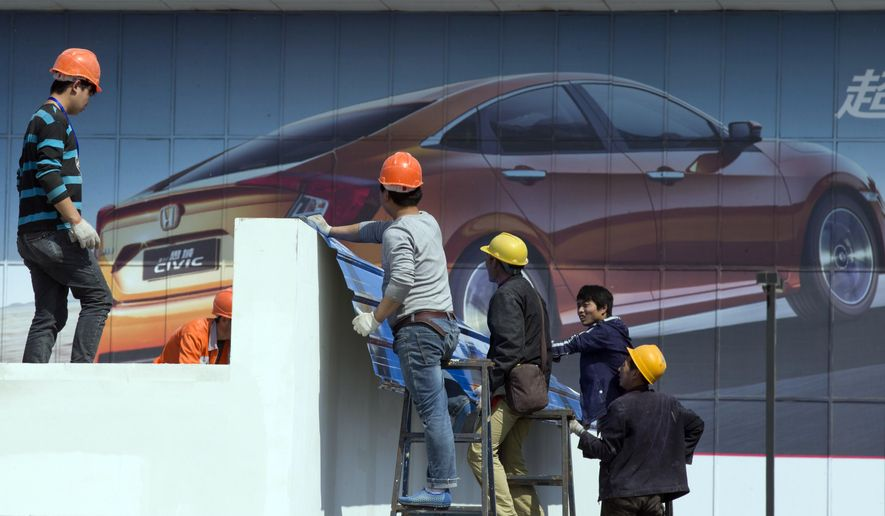 In this photo taken Wednesday, April 20, 2016, workers setup ahead of Auto China 2016 in Beijing, China. Industry figures released Jan. 12, 2017, show China's auto market had a bumper year in 2016 as sales grew by 15 percent, with drivers rushing to buy cars before a tax break expired at the end of the year. (AP Photo/Ng Han Guan)