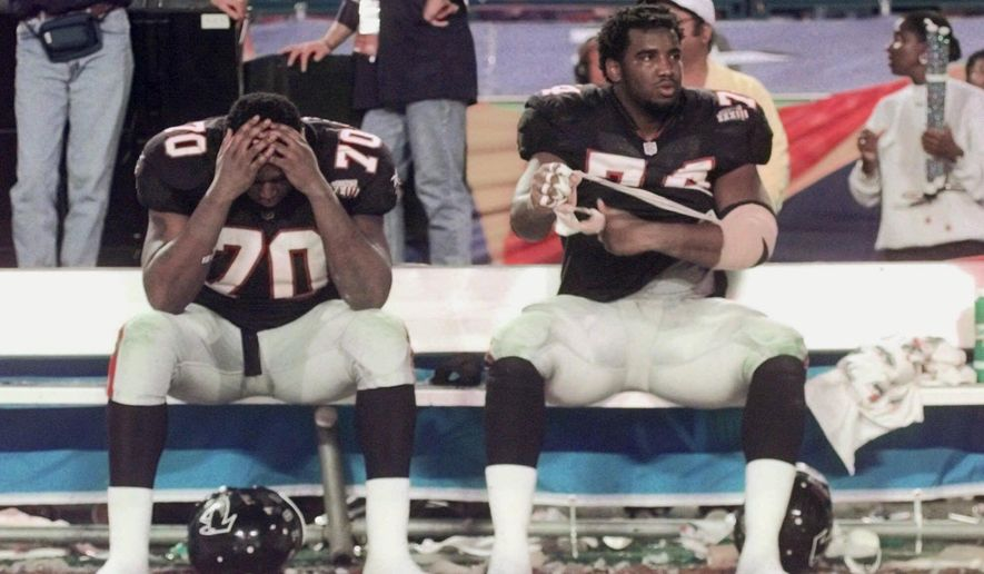 FILE - In this Jan. 31, 1999, file photo, Atlanta Falcons' Bob Whitfield (70) and Ephraim Salaam (74) sit on the bench surrounded by confetti following their 34-19 loss to the Denver Broncos in Super Bowl XXXIII, in Miami. The Falcons are in rare territory, indeed. For only the eighth time in franchise's 51-season history, they are among the final eight teams in the NFL playoffs. Of course, the Falcons have never won a Super Bowl title, a burden that hangs over this year's high-scoring team heading into Saturday's divisional round game against the Seattle Seahawks. (AP Photo/John Bazemore, File)