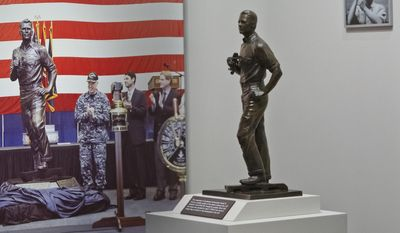 A maquette of Gerald R. Ford, left, is on display at the Gerald R. Ford Presidential Museum in Grand Rapids on Wednesday, Jan. 11, 2017. The maquette is a smaller version of a statue onboard the USS Gerald R. Ford supercarrier created by sculptor Brett Grill (Cory Morse/The Grand Rapids Press/MLive.com via AP)