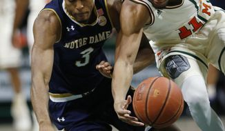 Notre Dame forward V.J. Beachem (3) and Miami guard Bruce Brown (11) reach for a loose ball during the first half of an NCAA college basketball game, Thursday, Jan. 12, 2017, in Coral Gables, Fla. (AP Photo/Wilfredo Lee)
