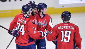 Washington Capitals left wing Alex Ovechkin, second from left, of Russia, celebrates his goal with defenseman John Carlson (74), center Nicklas Backstrom (19), of Sweden, and right wing T.J. Oshie, second from right, during the second period of an NHL hockey game against the Pittsburgh Penguins, Wednesday, Jan. 11, 2017, in Washington. (AP Photo/Nick Wass)