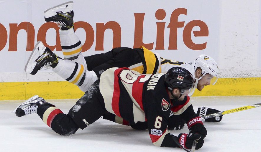 Pittsburgh Penguins' Scott Wilson falls to the ice with Ottawa Senators' Chris Wideman during the first period of an NHL hockey game Thursday, Jan. 12, 2017, in Ottawa, Ontario. (Sean Kilpatrick/The Canadian Press via AP)