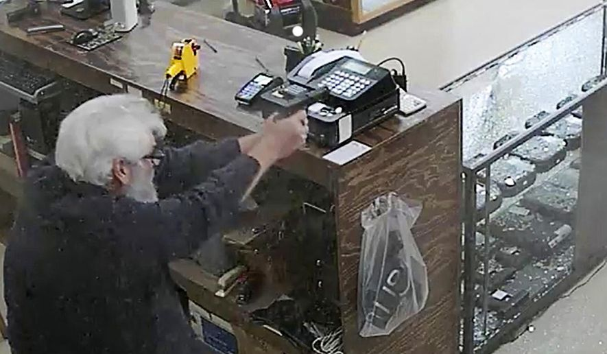 In this image made from surveillance video obtained Thursday, Jan. 12, 2017, Jimmy Groover, left, owner of Dixie Gun and Pawn in Mableton, Ga., shoots and kills a suspect during an robbery attempt on Dec. 26, 2016. The surveillance video obtained by The Associated Press shows Groover reacting quickly when the two men walked into his store. Cobb County police say the suspect who was shot, 30-year-old Donovan Chopin, died at the scene. (Jimmy Groover via AP)