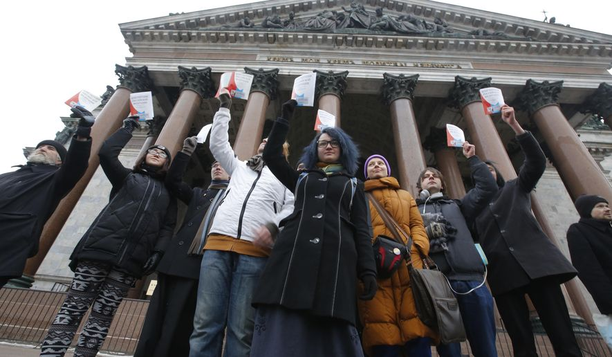 Protesters against the transfer of St. Isaac's Cathedral to the Russian Orthodox Church hold up the Constitution of the Russian Federation in front of the Cathedral in St. Petersburg, Russia, Thursday, Jan. 12, 2017. Authorities in Russia's second-largest city defend a controversial decision to give a city landmark cathedral to the Russian Orthodox Church. (AP Photo/Dmitri Lovetsky)