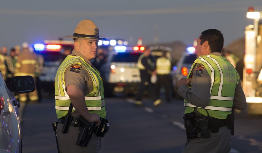 Emergency personnel gather at the scene where an Arizona Department of Public Safety trooper was shot, Thursday, Jan. 12, 2017, at the scene of a rollover accident on Interstate 10 near Tonopah, Ariz. An Arizona state trooper stopped to help at a car wreck along the remote highway Thursday when he was shot and wounded in an ambush by a man who was bashing the officer's head against the pavement until a passing driver shot him to death, authorities said.   The trooper suffered a severe wound to his shoulder and upper chest but he is expected to recover at a hospital.(Mark Henle/The Arizona Republic via AP)