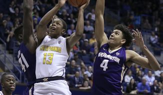 California's Charlie Moore, center, shoots between Washington's Matthew Atewe (41) and Matisse Thybulle (4) in the second half of an NCAA college basketball game Thursday, Jan. 12, 2017, in Berkeley, Calif. (AP Photo/Ben Margot)