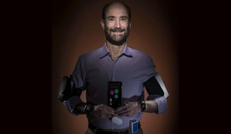 In this photo provided by Steve Fisch, Michael Snyder, professor and chair of genetics at the Stanford University School of Medicine sports wearable gadgets. Wearable gadgets gave a Snyder an early warning that he was getting sick before he ever felt any symptoms of Lyme disease.  (Steve Fisch via AP)