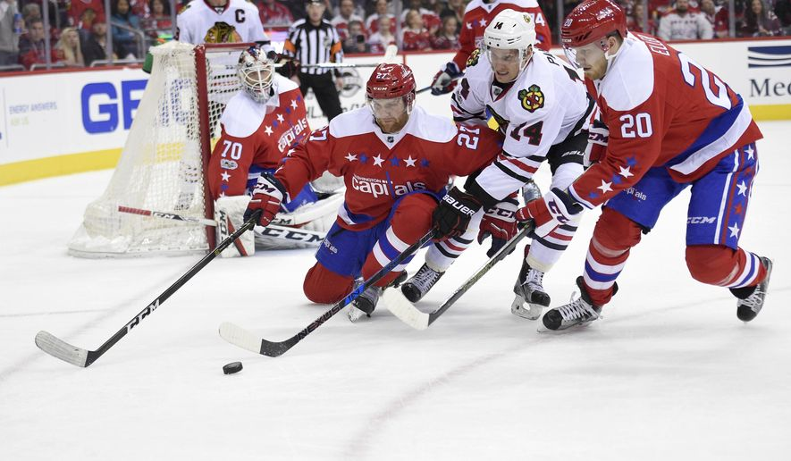 Washington Capitals defenseman Karl Alzner (27) and center Lars Eller (20), of Denmark, chase the puck against Chicago Blackhawks left wing Richard Panik (14), Slovakia, during the second period of an NHL hockey game, Friday, Jan. 13, 2017, in Washington. (AP Photo/Nick Wass)